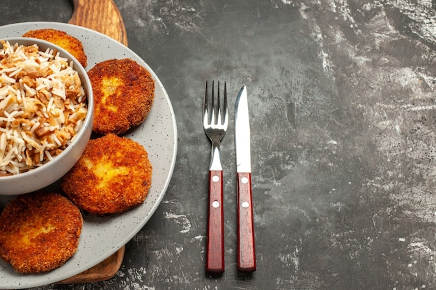 Top view fried cutlets with cooked rice on a dark desk dish meat rissole