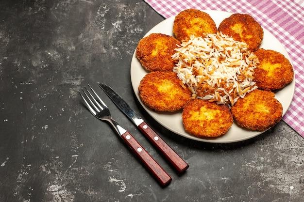 Vista dall'alto cotolette fritte con riso cotto su polpetta di piatto di carne scura scrivania