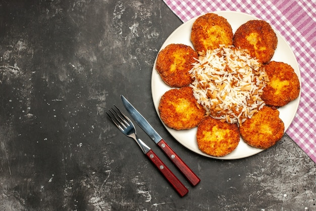 Top view fried cutlets with cooked rice on dark floor meat dish rissole