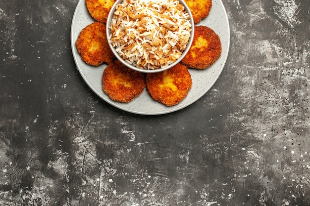 Top view fried cutlets with cooked rice on a dark surface dish rissole meat