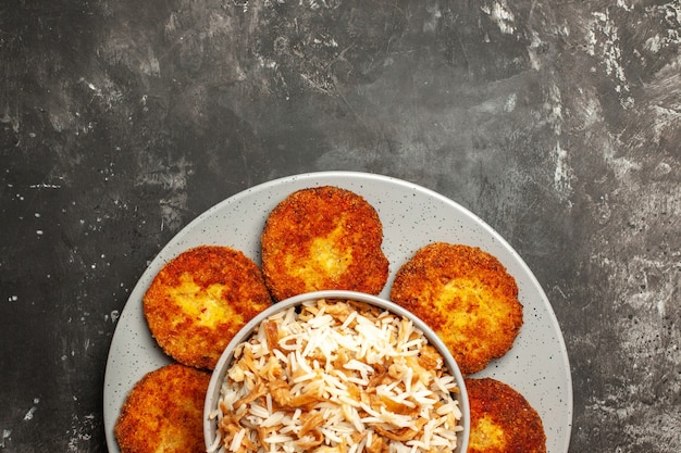 Top view fried cutlets with cooked rice on dark surface dish rissole meat
