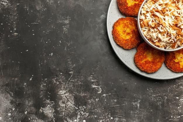 Vista dall'alto cotolette fritte con riso cotto sulla carne di polpetta piatto superficie scura