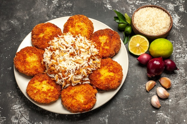 Top view fried cutlets with cooked rice on dark surface meat food dish rissole
