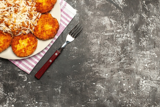 Top view fried cutlets with cooked rice on dark surface rissole dish meat