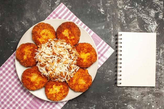 暗い床の肉料理のリッソールにご飯とカツレツを揚げた上面図