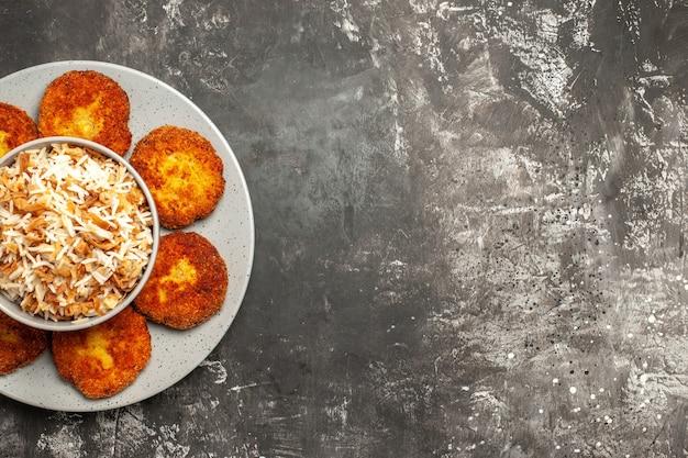 暗い光の表面の食品リッソール皿にご飯とカツレツを揚げた上面図