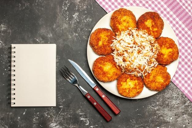 暗い表面の肉のリッソール皿にご飯とカツレツを揚げた上面図