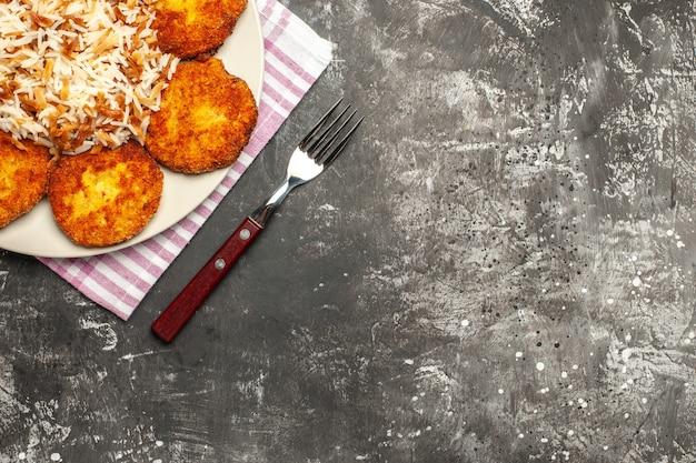 暗い表面のリッソール皿の肉にご飯とカツレツを揚げた上面図
