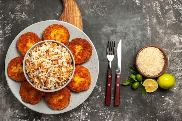 Вид сверху жареные котлеты с вареным рисом на темной поверхности блюдо, мясная котлета