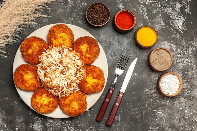 Vista dall'alto cotolette fritte con riso cotto e condimenti sul piatto di carne di cibo foto piano scuro