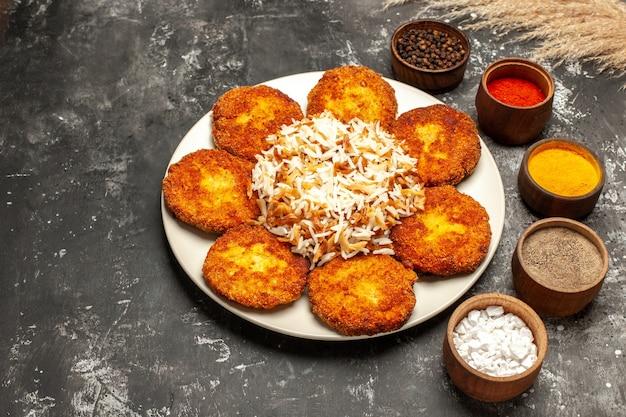 Vista dall'alto cotolette fritte con riso cotto e condimenti sulla carne del piatto di cibo superficie scura