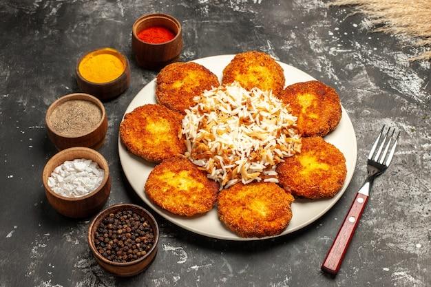 Vista dall'alto cotolette fritte con riso cotto e condimenti sulla carne della foto del piatto di cibo di superficie scura