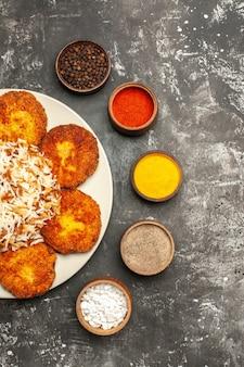Vista dall'alto cotolette fritte con riso cotto e condimenti sulla foto del piatto di cibo con superficie scura