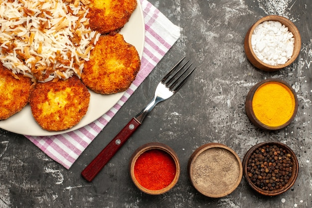 Top view fried cutlets with cooked rice and seasonings on a dark surface rissole dish meat