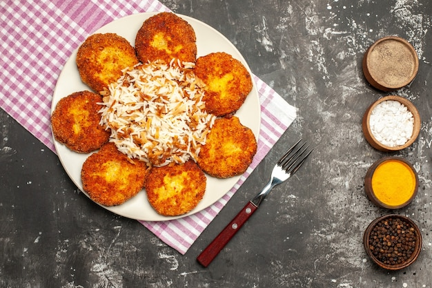 Top view fried cutlets with cooked rice and seasonings on dark surface rissole dish meat
