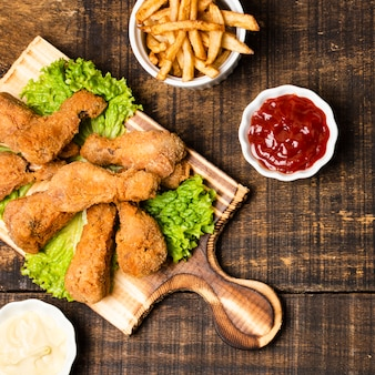 Top view of fried drumsticks with french fries