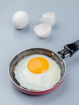 Top view of fried egg on a frying pan with cracked egg shell on white background