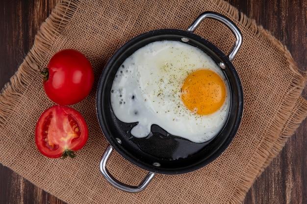Жареное яйцо на сковороде с помидорами на бежевой салфетке на деревянном фоне, вид сверху