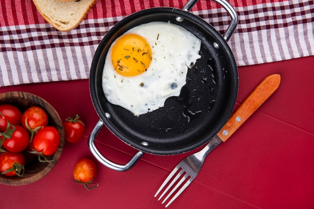 Top view of fried egg in pan with bread on plaid cloth and bowl of tomatoes and fork on red