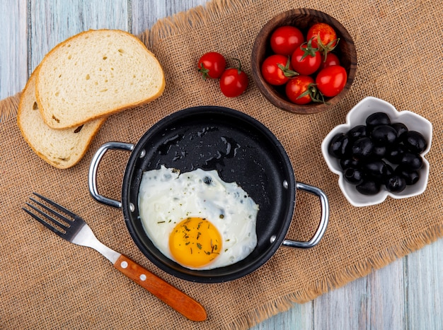 Top view of fried egg in pan with fork and bowl of tomato and bread slices on sackcloth and wood