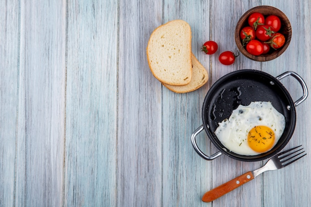 Top view of fried egg in pan with fork and bowl of tomato and bread slices on wood with copy space