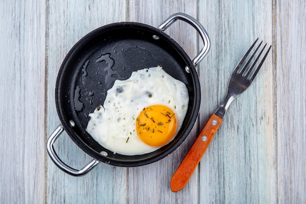 Top view of fried egg in pan with fork on wood