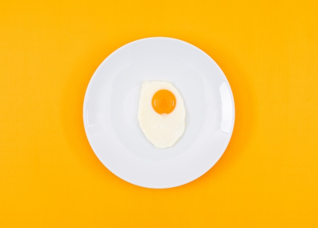 Top view of fried egg on white plate and on yellow surface horizontal