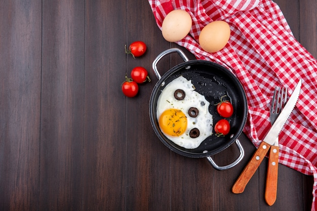 Top view of fried egg with tomatoes and olives in pan and fork with knife on plaid cloth and eggs with tomatoes on wood with copy space