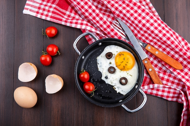 Top view of fried egg with tomatoes and olives in pan and fork with knife on plaid cloth with egg and egg shell with tomatoes on wood