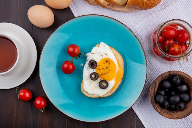 Top view of fried egg with tomatoes and olives in plate and bowls of tomato and olive bread on cloth with eggs and tea on wood