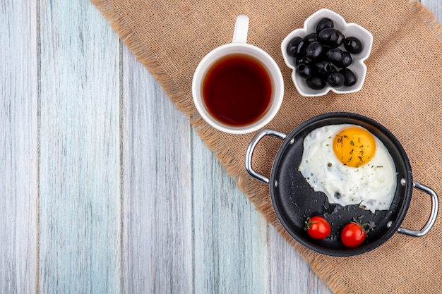 Top view of fried egg with tomatoes in pan and cup of tea with bowl of black olive on sackcloth and wood with copy space