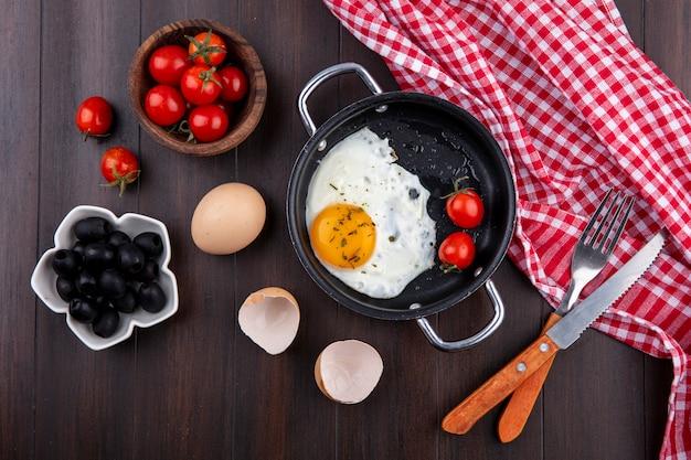 Vista dall'alto di uovo fritto con pomodori in padella e forchetta con coltello su panno plaid e uovo con guscio e ciotole di pomodoro e oliva su legno
