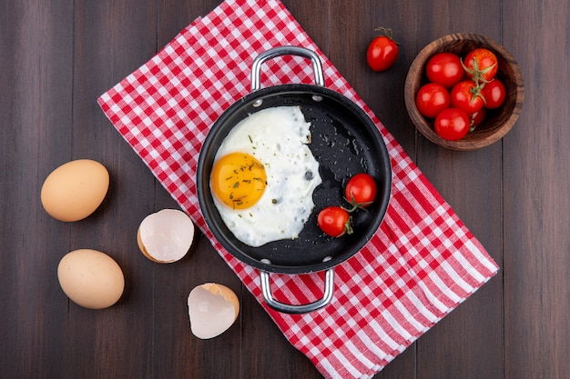 Top view of fried egg with tomatoes in pan on plaid cloth and eggs with shell and bowl of tomato on wooden surface