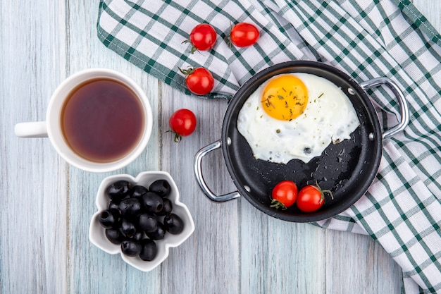 Top view of fried egg with tomatoes in pan and on plaid cloth with tea and olives on wooden surface