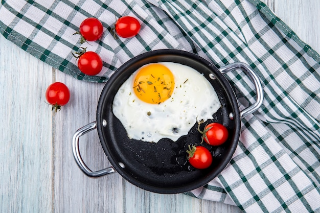 Top view of fried egg with tomatoes in pan and on plaid cloth on wood