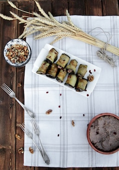 Top view of fried eggplant rolls with cream cheese walnuts and garlic on a plate on wooden table