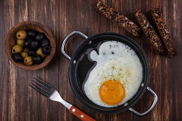 Вид сверху жареные яйца на сковороде с ломтиками черного хлеба и оливками с вилкой на деревянном фоне