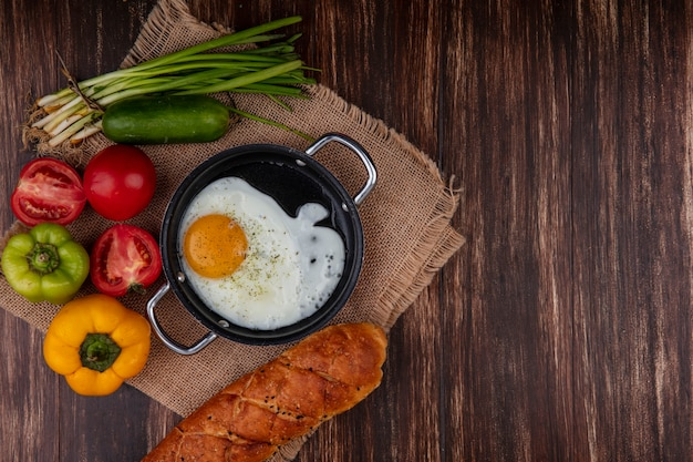 Top view fried eggs in a pan with green onions  tomatoes  cucumber  bell peppers and a loaf of bread  on a beige napkin  on a wooden background