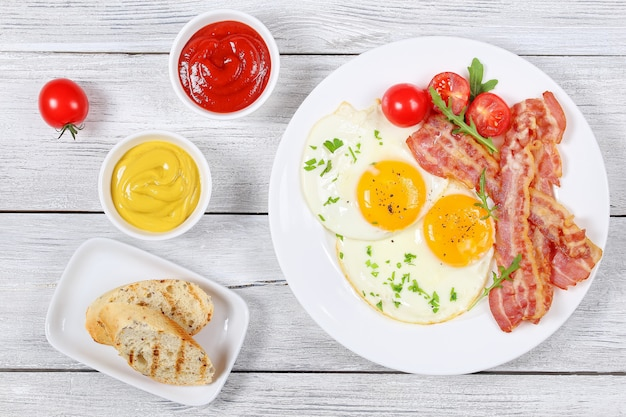 Top view of fried eggs with bacon and tomatoes