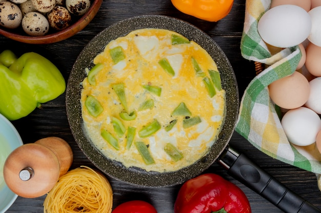 Top view of fried eggs with chopped slices of green bell pepper on a frying pan with fresh chicken eggs on a wooden background