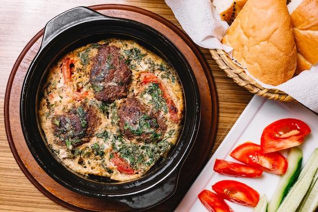 Вид сверху яичница с фрикадельками и зеленью в сковороде ломтиками помидора и огурца