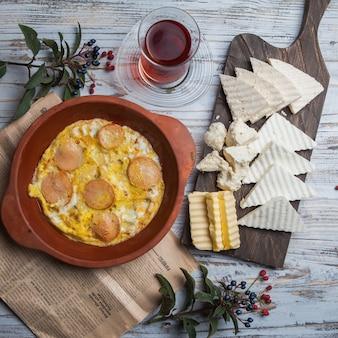 Вид сверху яичница с колбасками с сыром и стакан чая и рябины в глиняной тарелке