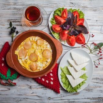 Vista dall'alto uova fritte con salsicce con pomodori tritati e formaggio e bicchiere di tè nel piatto di argilla