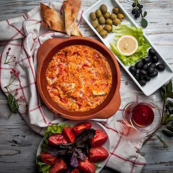 Vista dall'alto uova fritte con pomodori con bicchiere di tè e olive assortite e pomodori nel piatto di argilla