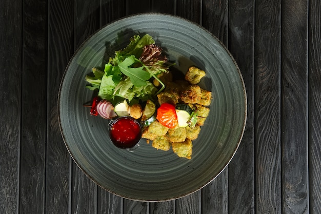 Top view of fried falafel with grilled vegetables on wooden skewer