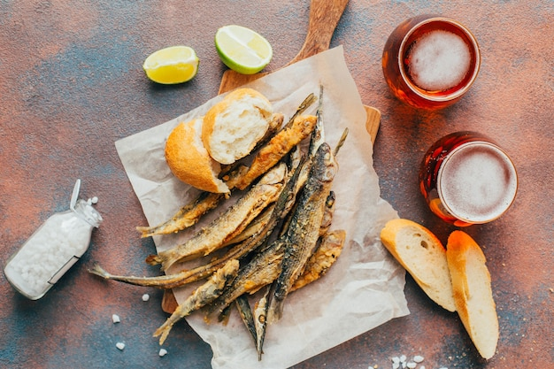 Top view of fried fish, beer, baguette, lemon and salt on concrete