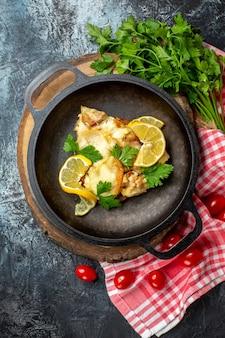 灰色の背景に赤と白の市松模様のテーブルクロスに木の板チェリートマトパセリの鍋で揚げ魚の上面図