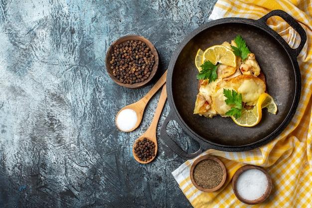 노란색 흰색 체크무늬 식탁보에 레몬과 파슬리를 넣은 팬에 튀긴 생선 튀김