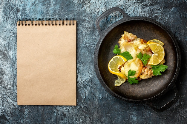 Top view fried fish in pan with lemon and parsley notebook on grey background