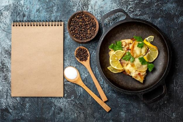 Vista dall'alto pesce fritto in padella con limone e prezzemolo spezie in cucchiai di legno pepe nero in una ciotola notebook su sfondo grigio